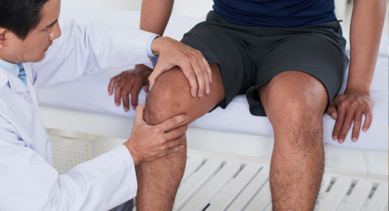 This image shows a doctor examining a patient's injured knee